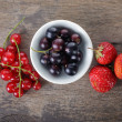 Organic garden berries on old wood table — Stock Photo