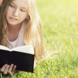 Young teenage girl reading book on grass — Stock Photo #38484389