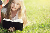Young teenage girl reading book on grass — Stock Photo