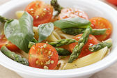 Italian pasta penne with tomatoes and asparagus — Stock Photo