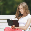 Young teenage girl reading book on bench — Stock Photo #39380791