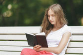 Young teenage girl reading book on bench — Foto Stock