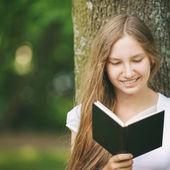 Young teenage girl reading book near tree — Stock Photo