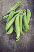 Heap of pea pods on old wood table — Stock Photo