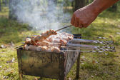 Man cooking shashlick outdoors — Stock Photo
