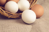 Chicken eggs in basket on burlap — Stock Photo