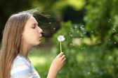 Teenage girl blowing a dandelion — Stock Photo