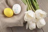 Ovos de páscoa de cor pastel com tulipas na mesa — Foto Stock