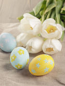 Pastel color easter eggs with tulips on table — Stock Photo