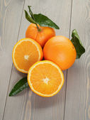 Ripe oranges on wooden table — Stock Photo