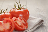 Fresh ripe tomatoes with halfs on wood table — Stock Photo