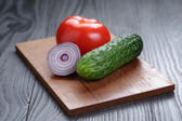 Tomato, cucumber and onion on black wood table — Stock Photo