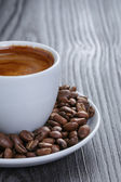 Cup of fresh espresso with beans — Stock Photo