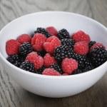 Ripe blackberries and raspberries in white bowl on old oak table — Stock Photo #50510431
