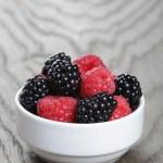 Ripe blackberries and raspberries in white bowl on old oak table — Stock Photo #50966817