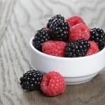 Ripe blackberries and raspberries in white bowl on old oak table — Stock Photo #50966821