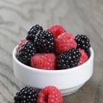 Ripe blackberries and raspberries in white bowl on old oak table — Stock Photo #50966823