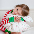Small girl in striped pajamas sitting on her bed — Stock Photo