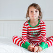 Small girl in striped pajamas sitting on her bed — Stock Photo #12123353