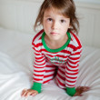 Portrait of small girl in pajamas sitting on the bed — Stock Photo