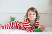 Petite fille en pyjama rayé, allongée sur son lit — Photo
