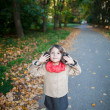 Stock Photo: Small girl outdoor in park hearing nature sounds. Above view