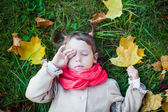 Nice toddler girl lying on the green grass with closed eyes — Stock Photo