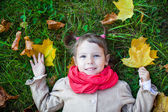 Nice toddler girl lying on the green grass in the park. Above view — Stock Photo