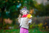 Nice toddler girl with yellow leaves bouquet — Stock Photo