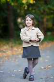 Nice preschooler girl in the autumn park with yellow leaves — Stock Photo