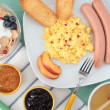 Stock Photo: Breakfast cereals jams honey with egg and sausage on table