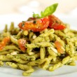 Italian pasta with pesto genovese and tomato sauce - Stock Photo
