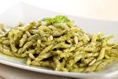 Italian pasta with pesto genovese and tomato sauce — Stock Photo