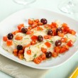 Cod fillets with tomatoes and olives on white plate — Stock Photo