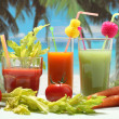 Vegetables juice in three glasses on the beach — Stock Photo