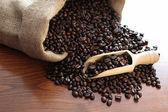 Coffee beans on wooden table — Stock Photo