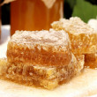 Close up honeycomb and honey in glass jar white wooden table — Stock Photo