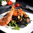 Black pasta spaghetti with seafood dark background — Stock Photo