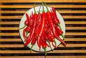 Group of hot spicy chilli peppers on a white plate — Stock Photo