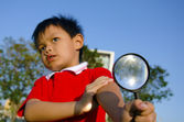 Child with a magnifying glass — Stockfoto