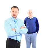 Portrait of a relaxed son standing with his father behind against white background — 图库照片