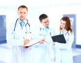 Portrait doctor smiling with colleagues in background — Stock Photo