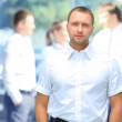 Handsome happy business man with colleagues at the back — Stock Photo