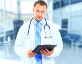 Portrait of doctor in white coat and stethoscope with arms crossed — Stock Photo