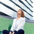 Business woman meditating and making yoga outdoor over building background  — ストック写真