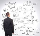 Mężczyzna patrząc na strategię biznesową na ścianie — Zdjęcie stockowe