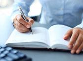 επιχειρηματίας κάνει μια σημείωση στο σημειωματάριο. — Φωτογραφία Αρχείου