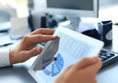 Business person analyzing financial statistics displayed on the tablet screen — Stock Photo