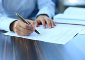 Businesswoman sitting at office desk signing a contract with shallow focus on signature — Stock Photo
