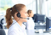 Beautiful young female call center operator with headset in office — Stock Photo